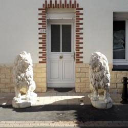 2 lions en pierre reconstituée devant une porte d'entrée